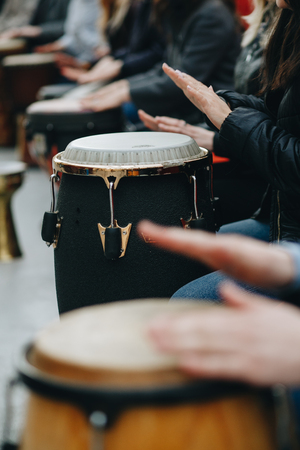 a large group of people play with African drums for the first time