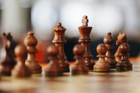 Chess pieces on a boart ready to play a game. Wood pieces of a game of chess on a board
