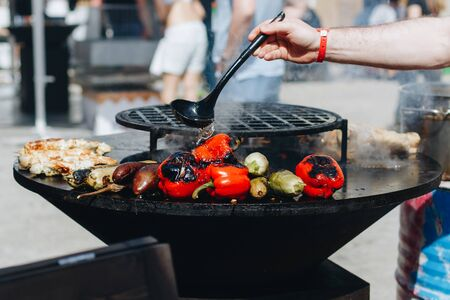 delicious vegetables grilling in open grill, outdoor kitchen. food festival in city. tasty food peppers zucchini roasting on basket, food-court. summer picnic
