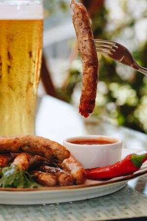 Appetizing beer snacks set close up. Assorted sausages, french f. Ries served with spicy tomato sauce and mustard on the board. Oktoberfest food, pub concept