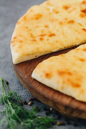Sliced pie with cheese on a wooden board on grey background. Khachapuri.