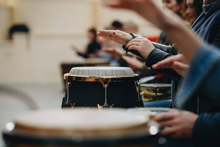 a large group of people play with African drums for the first time.