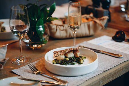 tableware Glasses, flower fork, knife served for dinner in restaurant with cozy interior Reklamní fotografie
