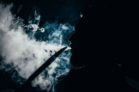 silhouette of a man exhaling smoke on a dark background closeup.