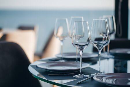 Glasses, flower fork, knife served for dinner in restaurant with cozy interior.