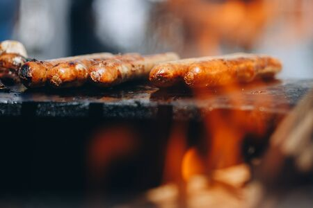 appetizing juicy chicken sausages on the grill close-up.