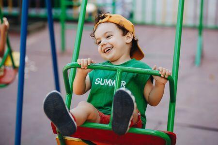 piękny mały chłopiec kręci się na letniej huśtawce z miejscem na tekst