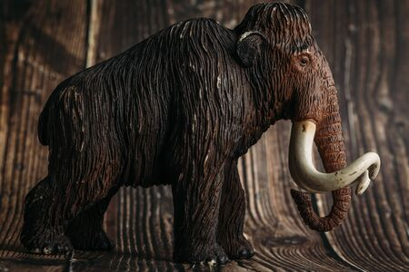figure of a toy mammoth on a wooden background.