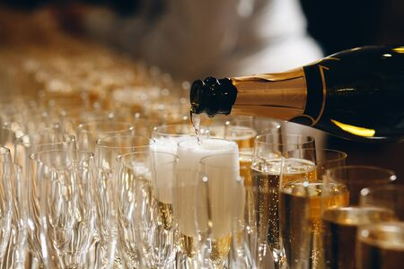 Bartender pouring champagne or wine into wine glasses on the table at the outdoors solemn wedding ceremony Imagens