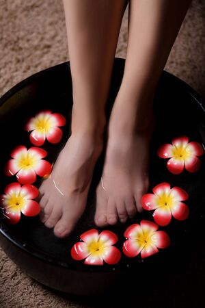 Close-up shot of a womans leg submerged in water with petals in a bowl. Beautiful womens legs in the Spa on the procedure of Thai massage. Banco de Imagens