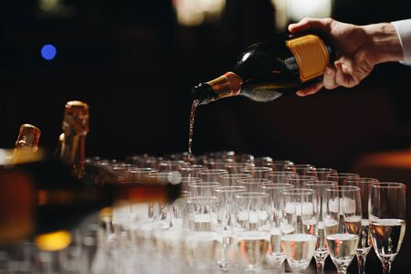 Bartender pouring champagne or wine into wine glasses on the table at the outdoors solemn wedding ceremony.