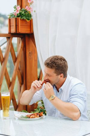 guy eats grilled chicken wings and drinks beer in a restaurant. Standard-Bild