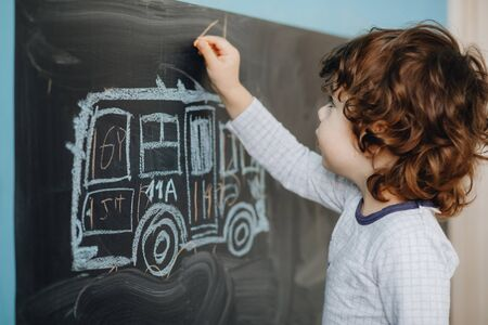 Curly little boy draws chalk on a board in his room.