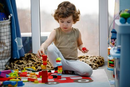 Little autistic boy playing with cubes at home