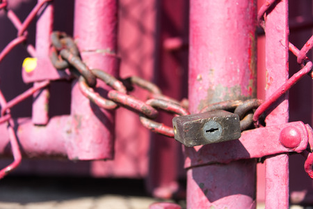 Old lock and chain on a pink fence