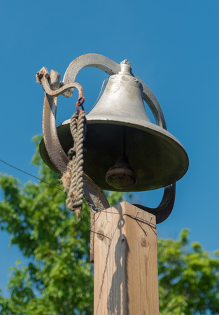 Big metal bell on a wooden poll Stock Photo
