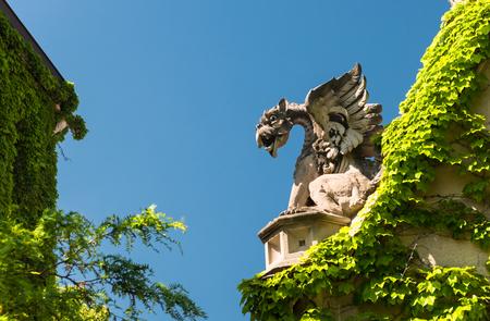 Big stone gargoyle on a gate in a park