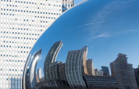 Large Chicago downtown building reflecting in Cloud Gate (glass mirror Chicago bean) Stock Photo