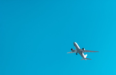 Big white plane flying in a blue sky Stock Photo