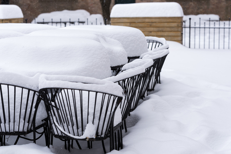 Metal chairs outside under a heavy snow