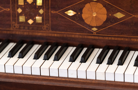 Old brown wooden piano with flower decoration