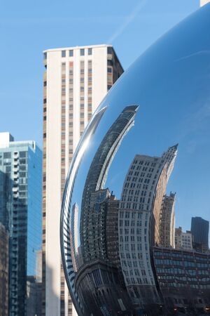 Large Chicago downtown building reflecting in Cloud Gate (glass mirror Chicago bean) Editorial