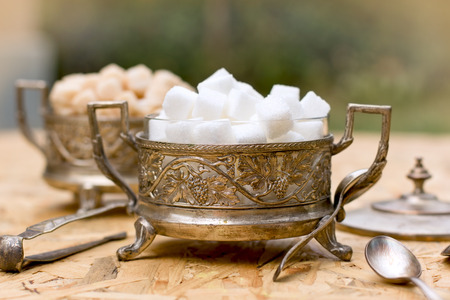 sugar cubes: White and yellow sugar cubes in silver containers - antique bowls Stock Photo