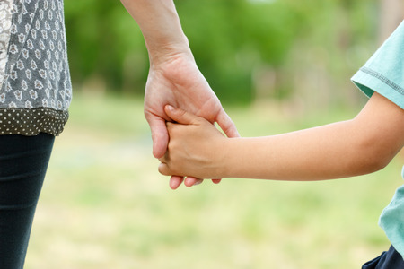 hands touch: Mother holding a hand of her son Stock Photo