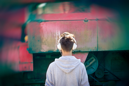 agricultural machinery: Young boy country boy listening to music in front of the agricultural machinery Stock Photo