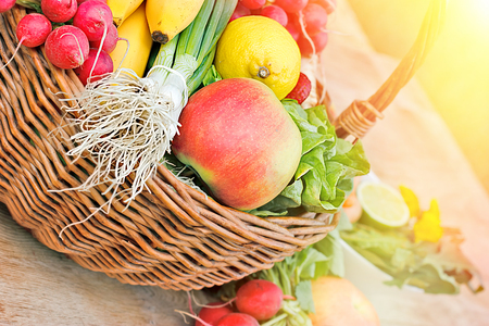 close up of onions in a basket: Fresh fruits and vegetables in wicker basket Stock Photo