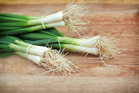 spring onions: Fresh organic spring onions on table Stock Photo
