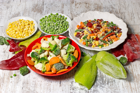 retain: Frozen vegetables in plate and bowl, frozen vegetables retain all the nutrients - healthy eating Stock Photo
