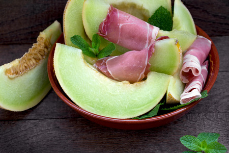 Melon with prosciutto and mint - delicious appetizer, meal - slices of melon (cantaloupe) and prosciutto Stock fotó