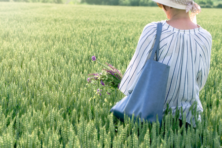 Woman in wheat field with meadow flowers in hand Banque d'images