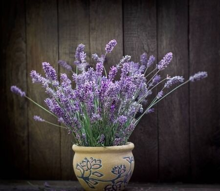 Bouquet of lavender flowers in vase on rustic table Stockfoto