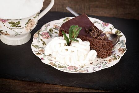 Chocolate cake with apricot jam and whipped cream and coffee Stock Photo