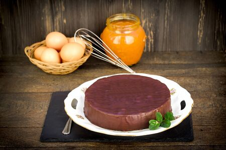 Chocolate cake with apricot jam on rustic table