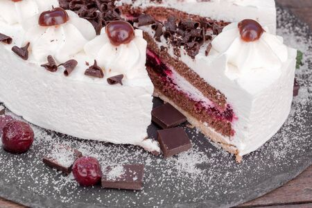 Slice of a Black forest cake, delicious cake with whipped cream, sour cherry and dark chocolate - Schwarzwald cake closeup