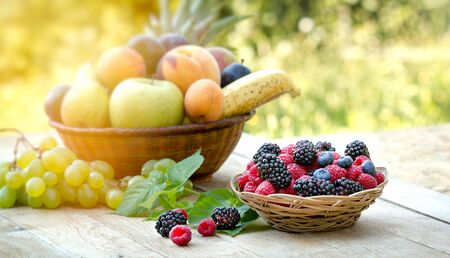 Forest fruit, forest berries in basket on wooden table