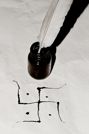 Traditional Swastik  with feather and ink bottle photo