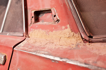 rusty car: Layer of putty on old rusty car