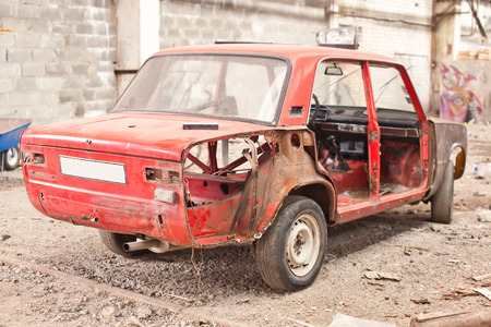 salvaging: Red old rusty car without doors