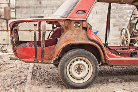 salvaging: Fragment of old red rusty car without doors Stock Photo