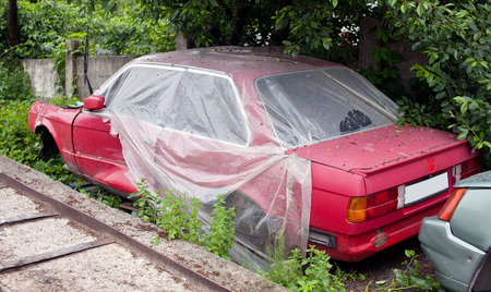 salvaging: Damaged red old car under plastic sheeting