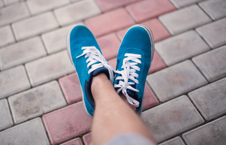lacing sneakers: Legs in blue shoes at tile