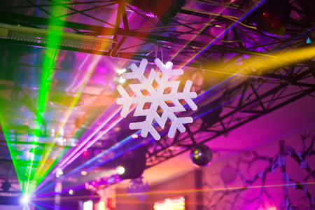 artificial lights: White artificial snowflake in rays of searchlights in the New Year interior nightclub