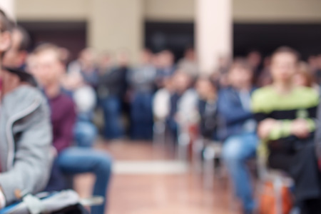 Many people at conference, blurred bokeh