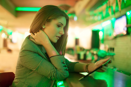 Young woman reading a digital tablet in cafe photo
