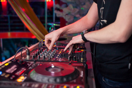 dj: DJ mixing music on console at the night club Stock Photo
