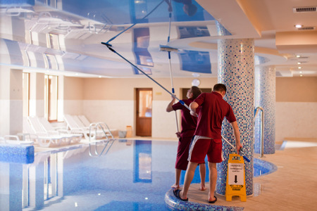 inground: YAREMCHE, UKRAINE - MARCH 18, 2015: Two men clean the ceiling of the swimming pool